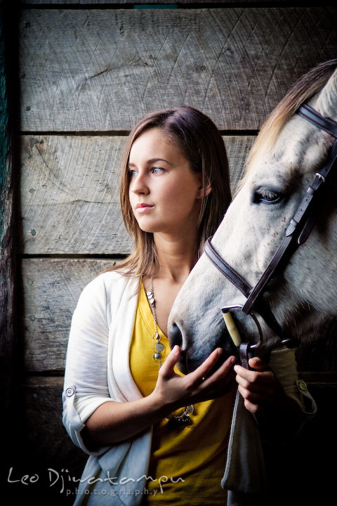 Girl holding horse, looking outside of stall. Annapolis Kent Island Maryland High School Senior Portrait Photography with Horse Pet by photographer Leo Dj