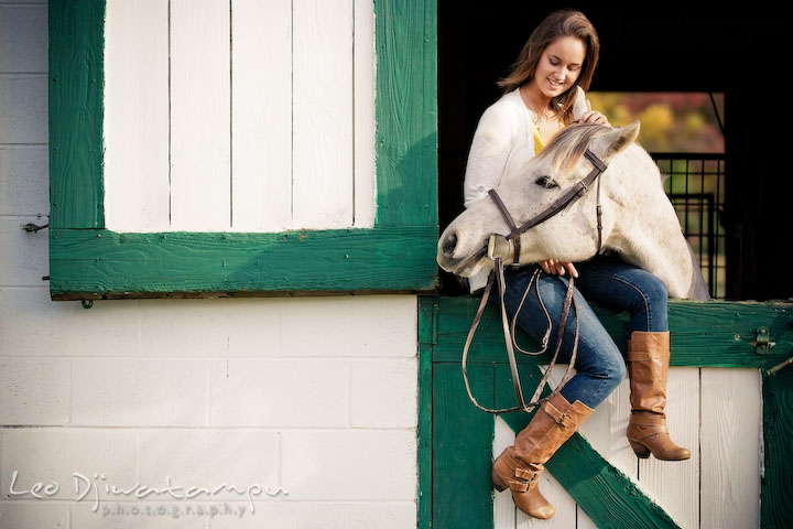 Girl sitting on stall door holding her horse. Annapolis Kent Island Maryland High School Senior Portrait Photography with Horse Pet by photographer Leo Dj