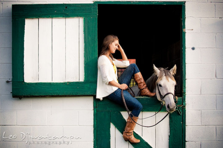 Girl sitting on stall door, brushing hair and smiling at her horse. Annapolis Kent Island Maryland High School Senior Portrait Photography with Horse Pet by photographer Leo Dj