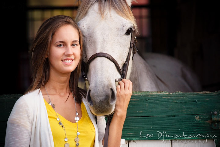 Girl posing with her horse looking at the camera. Annapolis Kent Island Maryland High School Senior Portrait Photography with Horse Pet by photographer Leo Dj