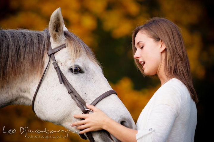 Girl owner talking with her mare. Annapolis Kent Island Maryland High School Senior Portrait Photography with Horse Pet by photographer Leo Dj