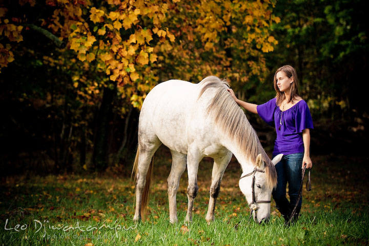 Girl standing next to horse who's eating grass. Annapolis Kent Island Maryland High School Senior Portrait Photography with Horse Pet by photographer Leo Dj