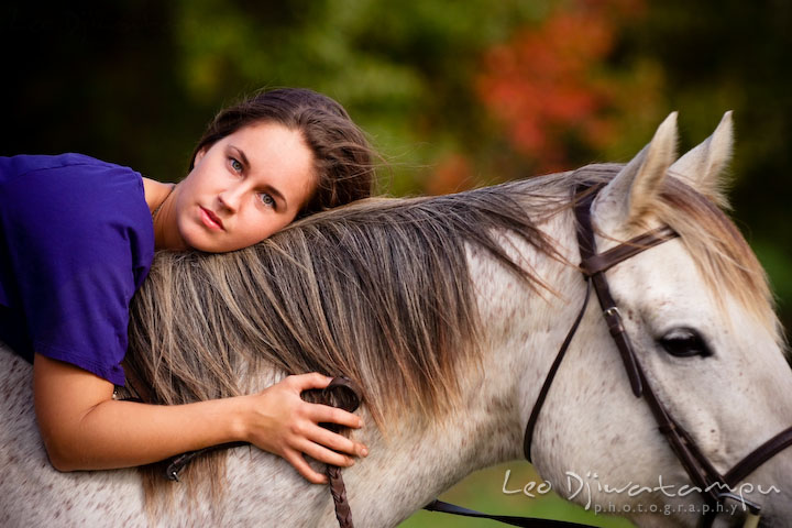 Girl owner laying on horse. Annapolis Kent Island Maryland High School Senior Portrait Photography with Horse Pet by photographer Leo Dj