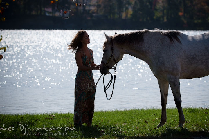 Sihouette of a girl talking to her mare by the water. Annapolis Kent Island Maryland High School Senior Portrait Photography with Horse Pet by photographer Leo Dj