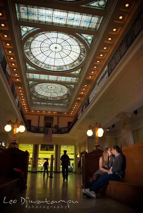 Engaged couple kissing on a bench inside the station under the beautiful stained glass domes. Pennsylvania Train Station Baltimore Maryland pre-wedding engagement photo session by wedding photographer Leo Dj Photography.
