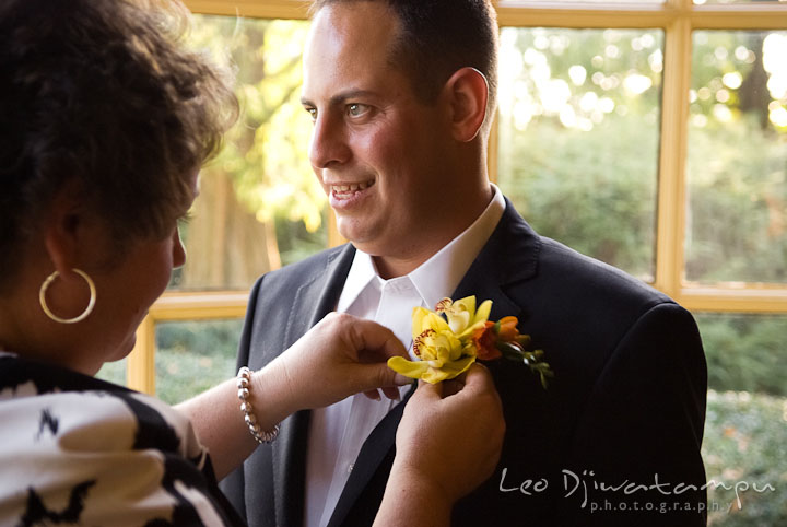 Wedding coordinator put on boutonniere on Groom. Mariott Aspen Wye River Conference Center Wedding photos at Queenstown Eastern Shore Maryland, by photographers of Leo Dj Photography.