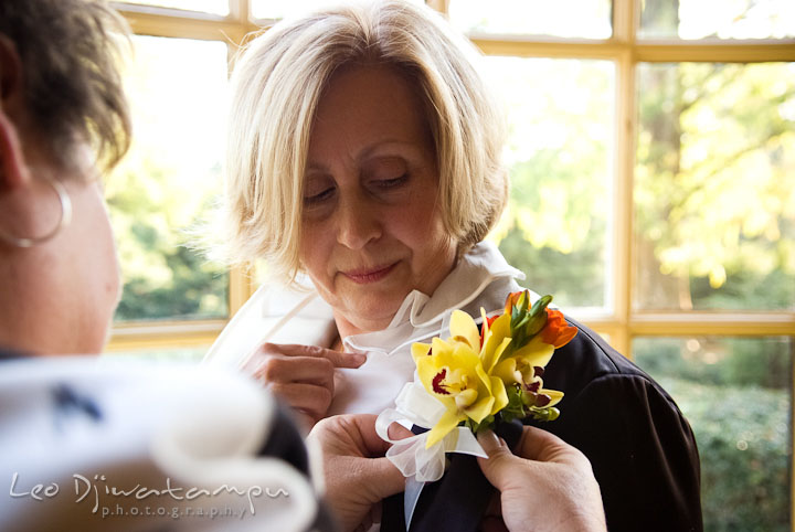 Wedding coordinator put on boutonniere on Mother of Groom. Mariott Aspen Wye River Conference Center Wedding photos at Queenstown Eastern Shore Maryland, by photographers of Leo Dj Photography.