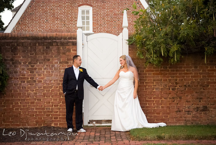 Bride and Groom holding hands, looking at each other by antique door. Mariott Aspen Wye River Conference Center Wedding photos at Queenstown Eastern Shore Maryland, by photographers of Leo Dj Photography.