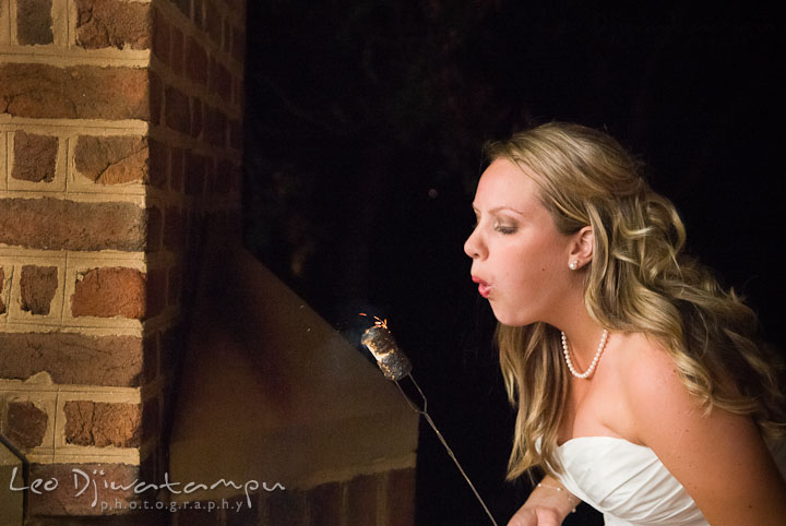 Bride blowing fire from marshmallows for s'mores. Mariott Aspen Wye River Conference Center Wedding photos at Queenstown Eastern Shore Maryland, by photographers of Leo Dj Photography.