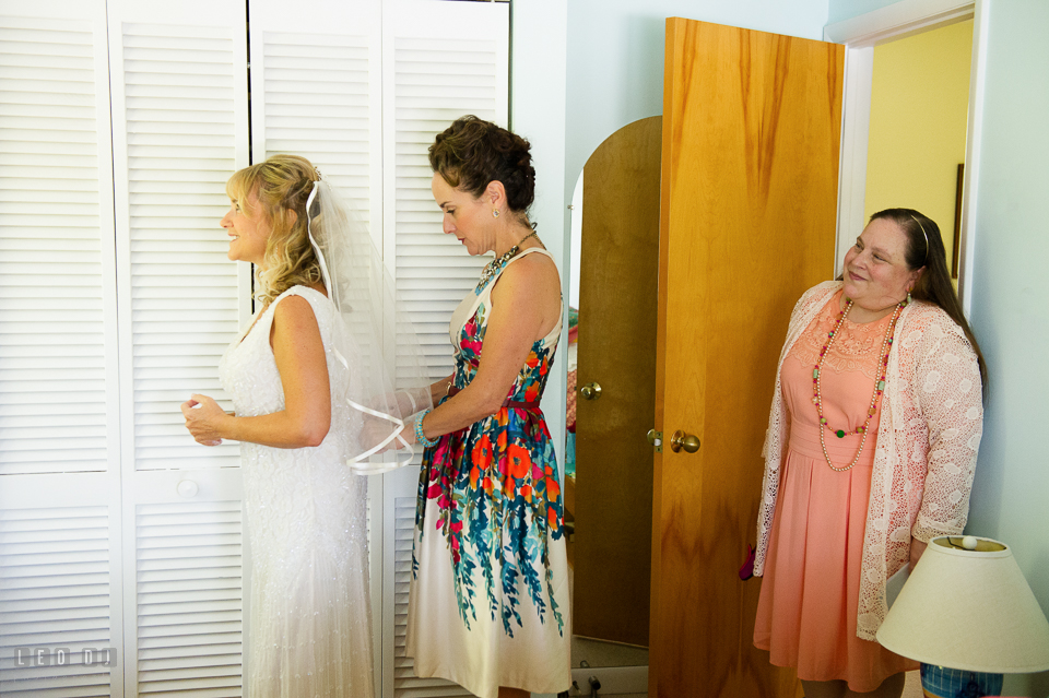 At home backyard sister help Bride put on wedding gown photo by Leo Dj Photography