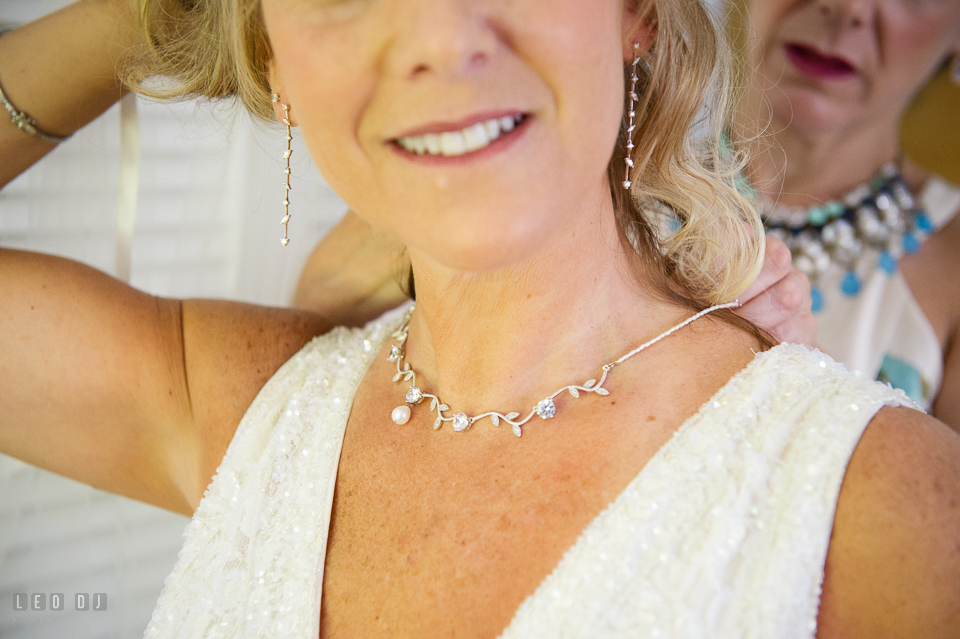 At home backyard wedding sister help Bride put on necklace photo by Leo Dj Photography