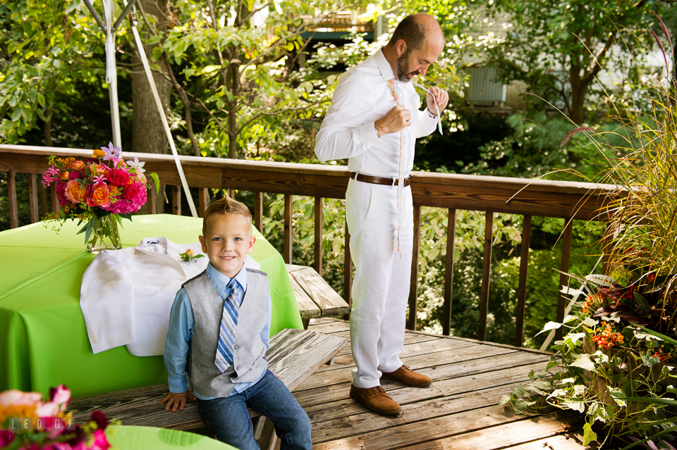 At home backyard wedding Groom putting on tie with nephew photo by Leo Dj Photography