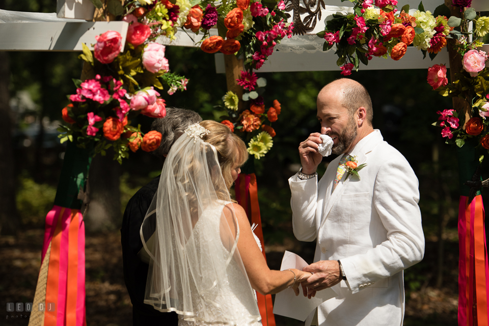 At home backyard wedding Groom wipe of tear while reciting vow at ceremony photo by Leo Dj Photography