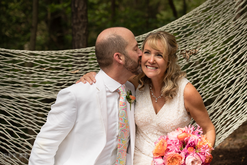 At home backyard wedding Groom kiss Bride on hammock laughing photo by Leo Dj Photography