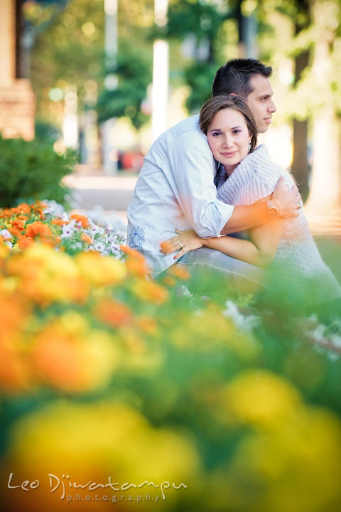 Engaged girl hugged by her fiancee by the flower bed. Candid Old Town Alexandria Virginia Engagement Photography Session by Wedding Photographer Leo Dj