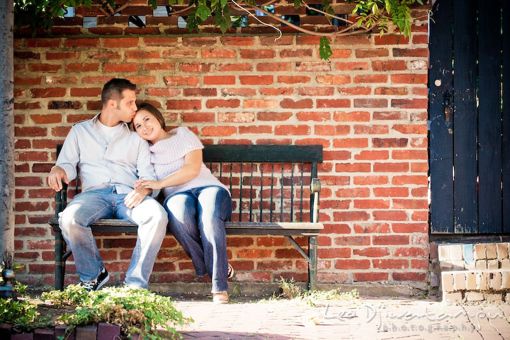 Engaged guy kissed his fiancee on a bench outside. Candid Old Town Alexandria Virginia Engagement Photography Session by Wedding Photographer Leo Dj