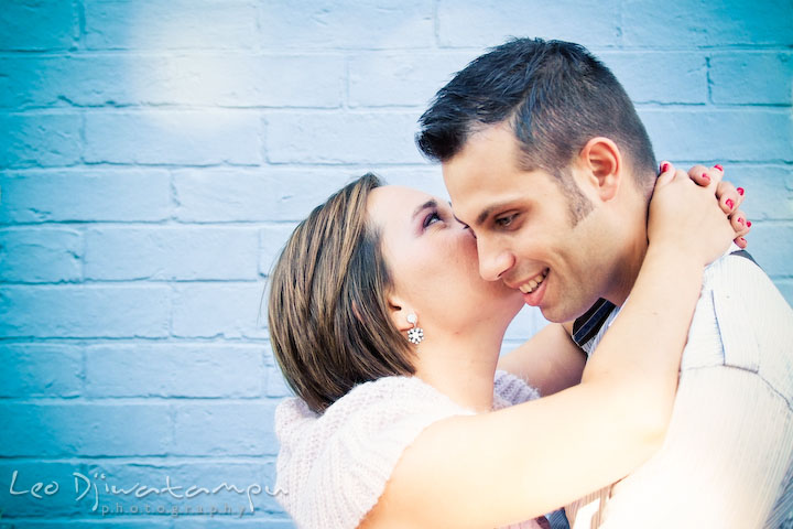 Engaged girl kissed her fiancee by a light marine blue brick wall. Candid Old Town Alexandria Virginia Engagement Photography Session by Wedding Photographer Leo Dj