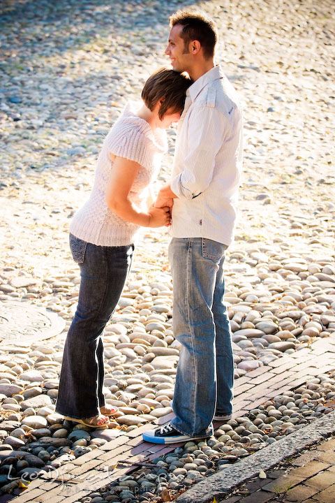 Engaged couple holding hands, laughing, on a cobble stone street. Candid Old Town Alexandria Virginia Engagement Photography Session by Wedding Photographer Leo Dj