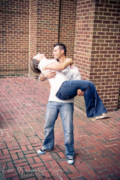 Engaged guy lift up his fiancee, laughing. Candid Old Town Alexandria Virginia Engagement Photography Session by Wedding Photographer Leo Dj