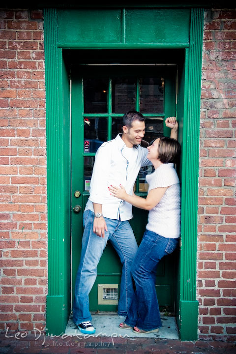 Engaged couple talking by a green door and frame. Candid Old Town Alexandria Virginia Engagement Photography Session by Wedding Photographer Leo Dj