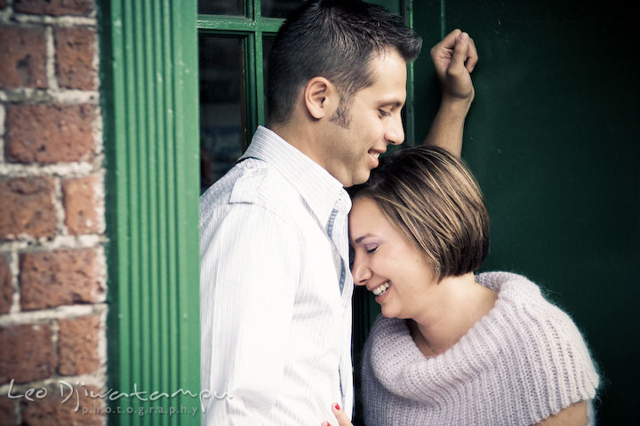 Engaged couple cuddling and laughing. Candid Old Town Alexandria Virginia Engagement Photography Session by Wedding Photographer Leo Dj