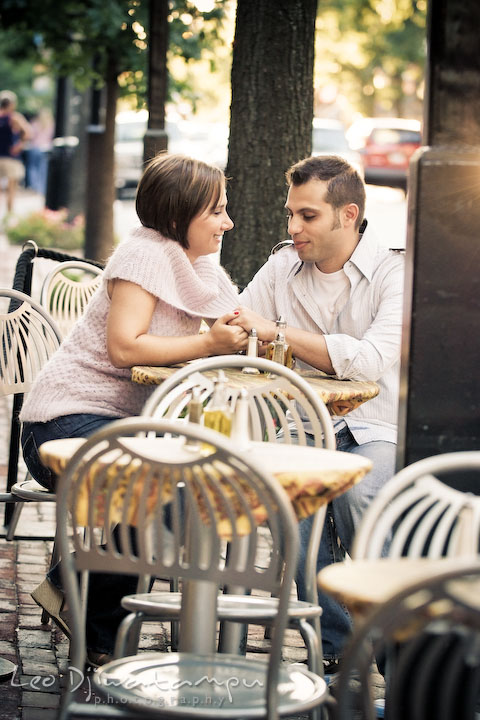 Engaged couple holding hand at an outdoor restaurant table. Candid Old Town Alexandria Virginia Engagement Photography Session by Wedding Photographer Leo Dj