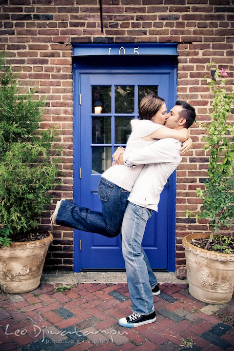 Engaged guy lifted up his fiance and kissed by a blue door. Candid Old Town Alexandria Virginia Engagement Photography Session by Wedding Photographer Leo Dj