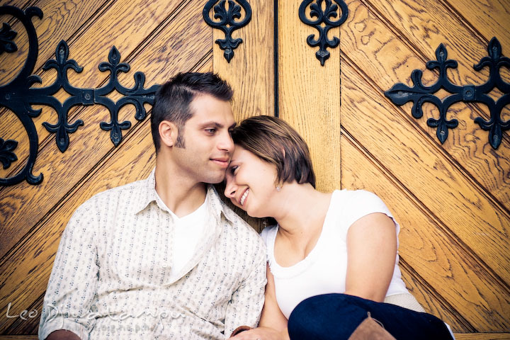 Engaged guy and girl sitting and cuddling by a large antique wooden door. Washington DC, Smithsonian, The Mall Pre-wedding Engagement Session Photographer Leo Dj Photography