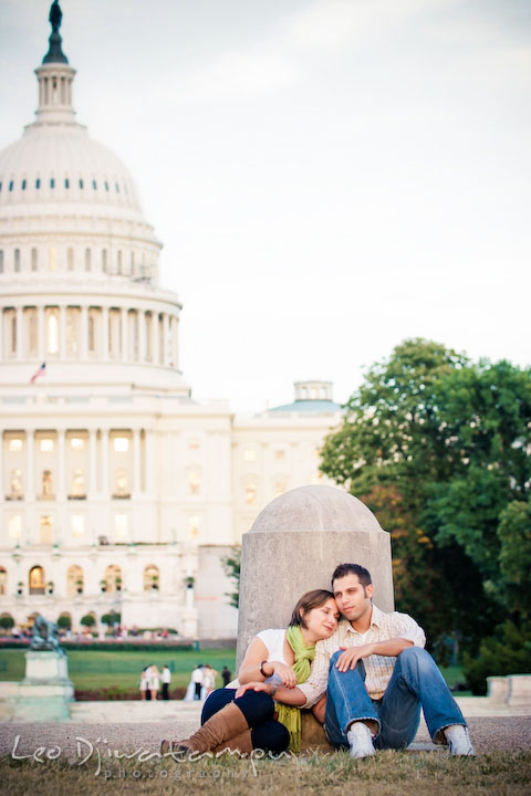 Engaged girl sitting on grass, leaning head on her fiancee's shoulder. The Capitol in the background. Washington DC, Smithsonian, The Mall Pre-wedding Engagement Session Photographer Leo Dj Photography