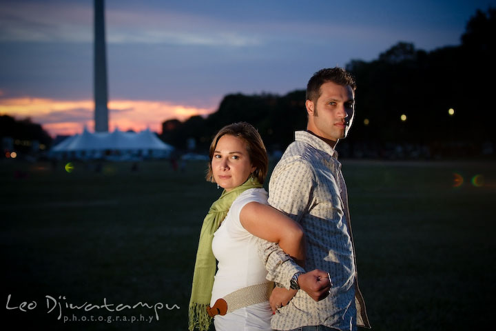 Engaged girl and guy back to back locking their elbows. Washington Monument in the background. Washington DC, Smithsonian, The Mall Pre-wedding Engagement Session Photographer Leo Dj Photography