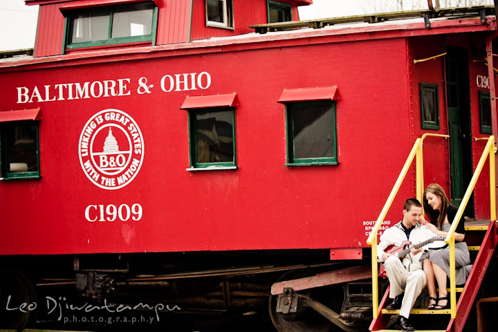 Engaged guy and girl sitting by a red caboose. Pre-Wedding Engagement Photo Session at Sykesville Maryland with Train Rail and Caboose by wedding photographer Leo Dj Photography