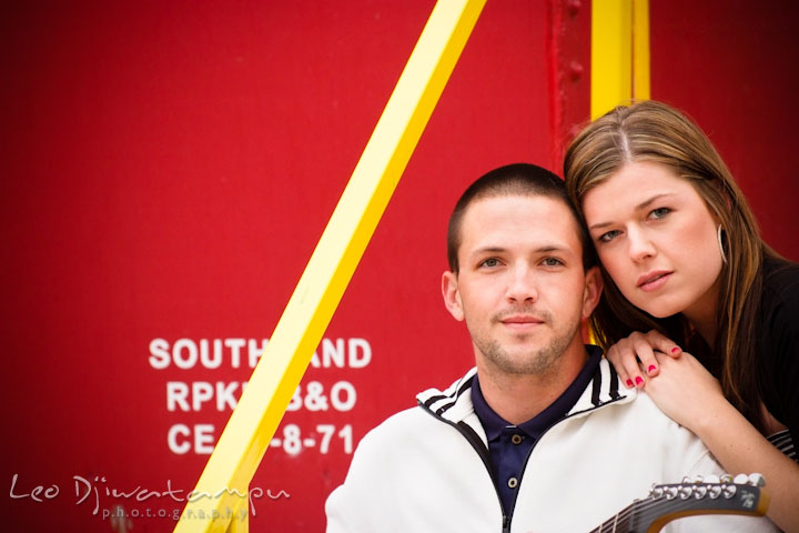 Engaged girl and her fiancé posing in front of a red caboose. Pre-Wedding Engagement Photo Session at Sykesville Maryland with Train Rail and Caboose by wedding photographer Leo Dj Photography