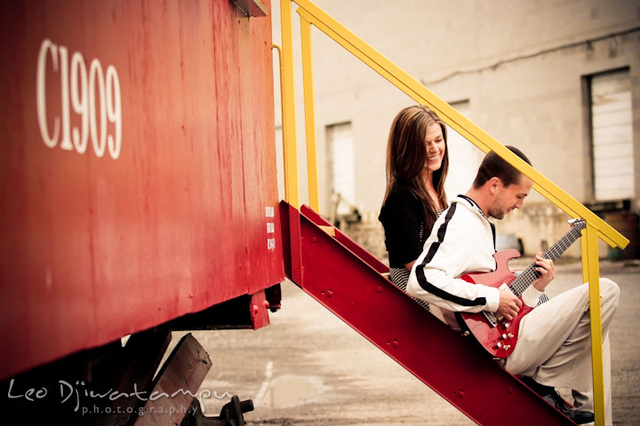 Engaged guy playing his red electric guitar and his fiancée laughing. Pre-Wedding Engagement Photo Session at Sykesville Maryland with Train Rail and Caboose by wedding photographer Leo Dj Photography