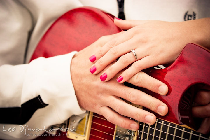Engaged guy and girl showing of their diamond engagement ring with a red electric guitar. Pre-Wedding Engagement Photo Session at Sykesville Maryland with Train Rail and Caboose by wedding photographer Leo Dj Photography