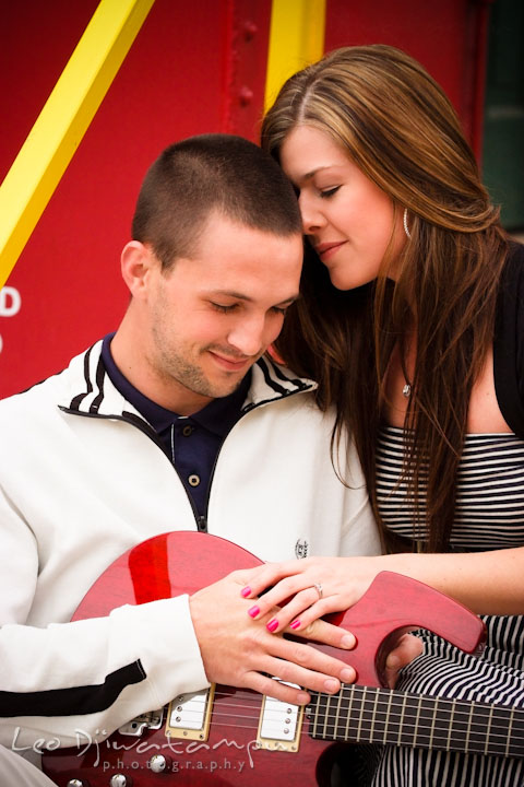 Engaged couple cuddling by a red caboose. Pre-Wedding Engagement Photo Session at Sykesville Maryland with Train Rail and Caboose by wedding photographer Leo Dj Photography