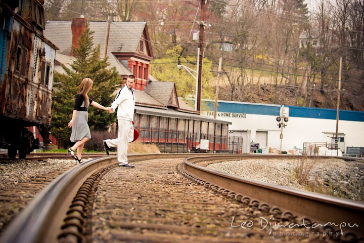 Engaged guy leading his fiancée through train tracks. Pre-Wedding Engagement Photo Session at Sykesville Maryland with Train Rail and Caboose by wedding photographer Leo Dj Photography