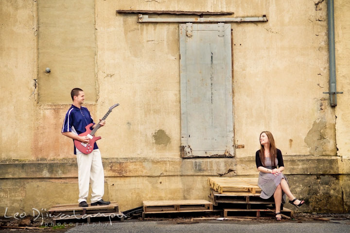 Engaged guy playing guitar to his fiancée. Pre-Wedding Engagement Photo Session at Sykesville Maryland with Train Rail and Caboose by wedding photographer Leo Dj Photography