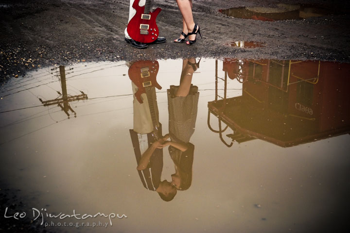 Engaged girl cuddling with her fiancé. Image of them and red caboose reflected on a puddle. Pre-Wedding Engagement Photo Session at Sykesville Maryland with Train Rail and Caboose by wedding photographer Leo Dj Photography