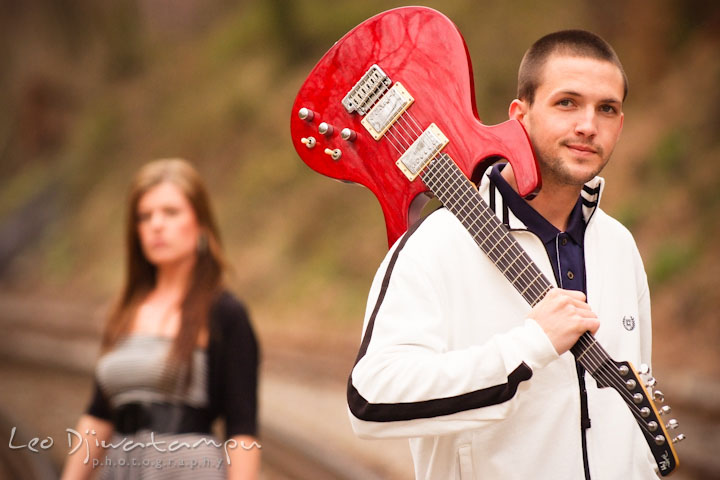 Engaged guy posing with his red electric guitar. His fiancée in the background. Pre-Wedding Engagement Photo Session at Sykesville Maryland with Train Rail and Caboose by wedding photographer Leo Dj Photography