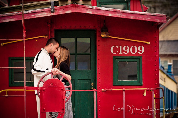 Engaged guy and girl kissing in a red caboose. Pre-Wedding Engagement Photo Session at Sykesville Maryland with Train Rail and Caboose by wedding photographer Leo Dj Photography