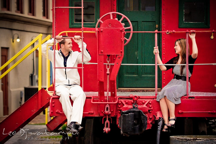 Engaged guy and his fiancée on a red caboose looking at each other and smiling. Pre-Wedding Engagement Photo Session at Sykesville Maryland with Train Rail and Caboose by wedding photographer Leo Dj Photography