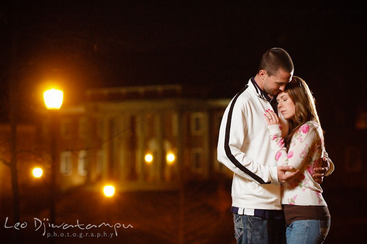 Engaged guy and girl cuddling in the evening by the building and street lights. Pre-Wedding Engagement Photo Session at Sykesville Maryland with Train Rail and Caboose by wedding photographer Leo Dj Photography