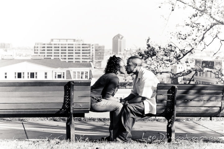 couple holding hand and kissing on bench, overlooking at the city. Federal Hill Park Baltimore pre-wedding engagement portrait