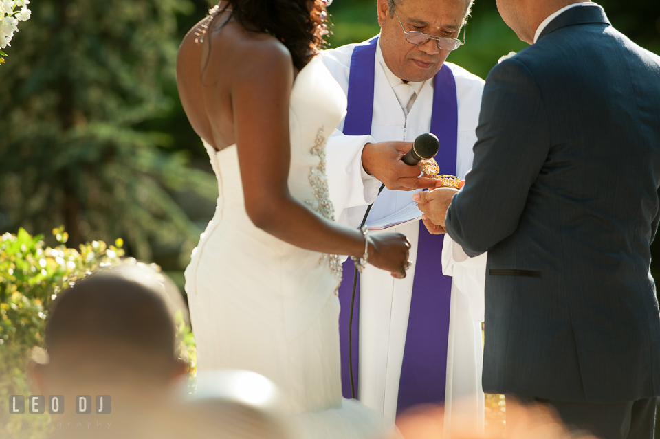 The wedding officiant, Reverend Julian Bermudez, opening the gold coin box. Falls Church Virginia 2941 Restaurant wedding ceremony and reception photo, by wedding photographers of Leo Dj Photography. http://leodjphoto.com