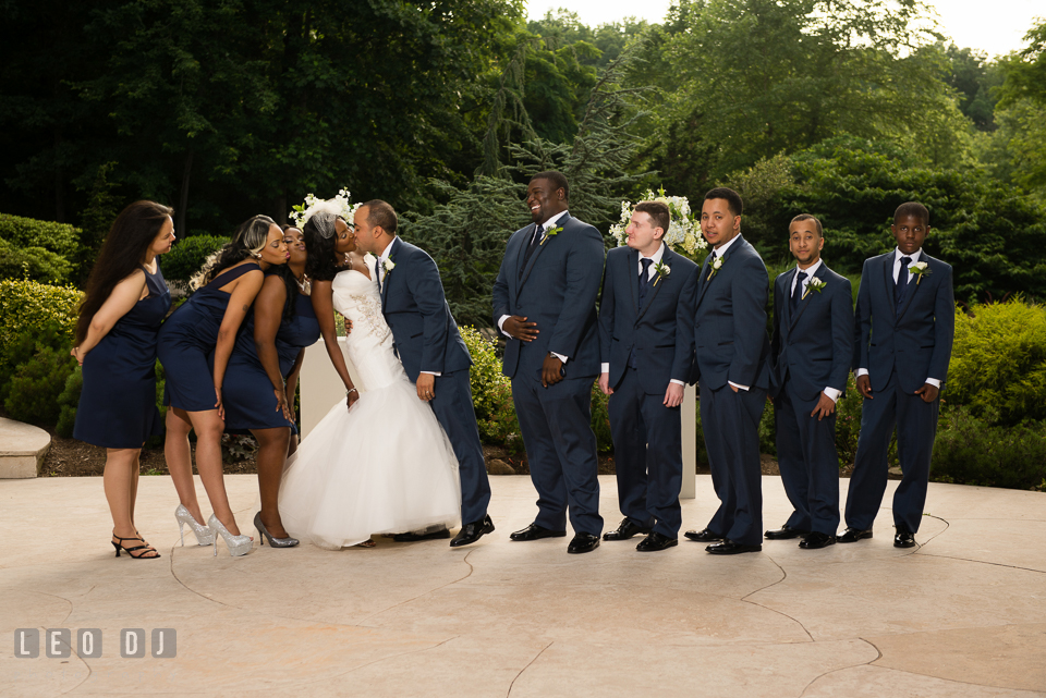 The Bride and Groom kissing and watched by the bridal party and groom's party. Falls Church Virginia 2941 Restaurant wedding ceremony and reception photo, by wedding photographers of Leo Dj Photography. http://leodjphoto.com