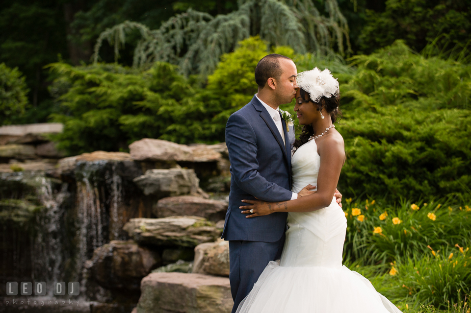 Groom kissed Bride on forehead by the outdoor rock garden with waterfall. Falls Church Virginia 2941 Restaurant wedding ceremony and reception photo, by wedding photographers of Leo Dj Photography. http://leodjphoto.com