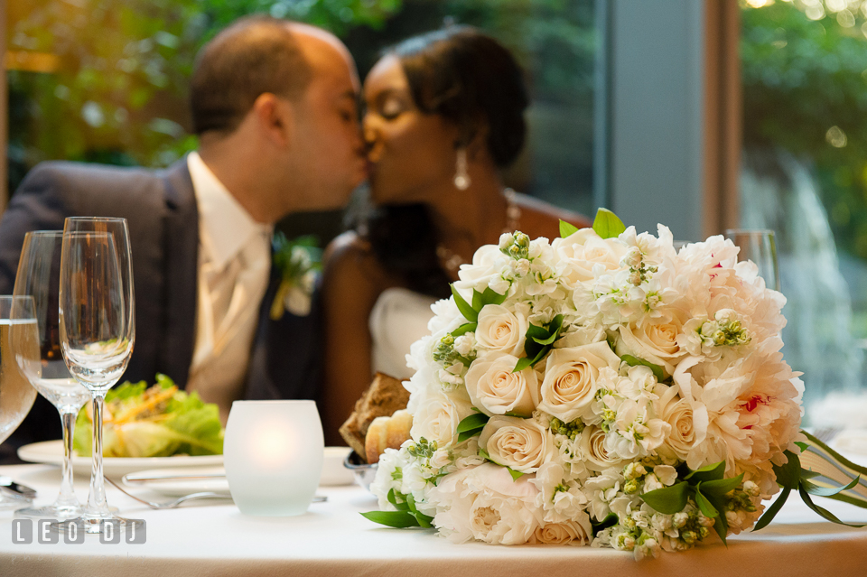 Bride and Groom kissed behind the sweetheart table with the large pink rose and white peonies floral bouquet by florist Highway to Hill. Falls Church Virginia 2941 Restaurant wedding ceremony and reception photo, by wedding photographers of Leo Dj Photography. http://leodjphoto.com