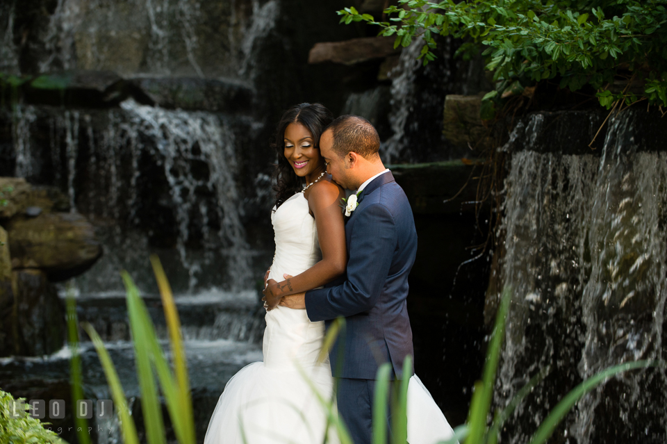Bride and Groom cuddling by the tall waterfall. Falls Church Virginia 2941 Restaurant wedding ceremony and reception photo, by wedding photographers of Leo Dj Photography. http://leodjphoto.com