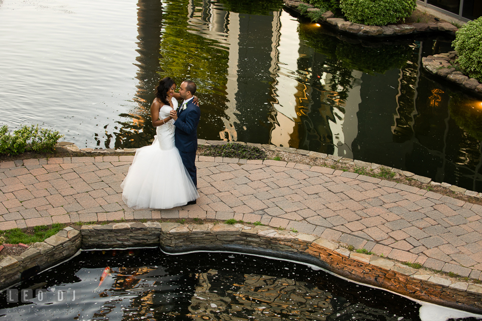 Slow dance by the pond with koi fishes before wedding reception. Falls Church Virginia 2941 Restaurant wedding ceremony and reception photo, by wedding photographers of Leo Dj Photography. http://leodjphoto.com