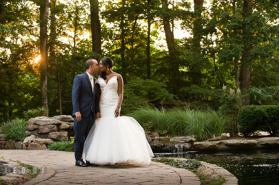 Bride and Groom kissing by the woods and pond during sunset. Falls Church Virginia 2941 Restaurant wedding ceremony and reception photo, by wedding photographers of Leo Dj Photography. http://leodjphoto.com